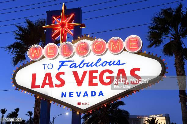 Purple and gold lights flicker around the Welcome to Fabulous Las Vegas sign as a tribute to nine victims killed in a helicopter crash on Sunday in...
