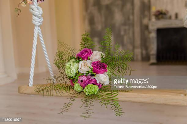 purple and green flower bouqet lying on swing - purple roses bouquet stock pictures, royalty-free photos & images
