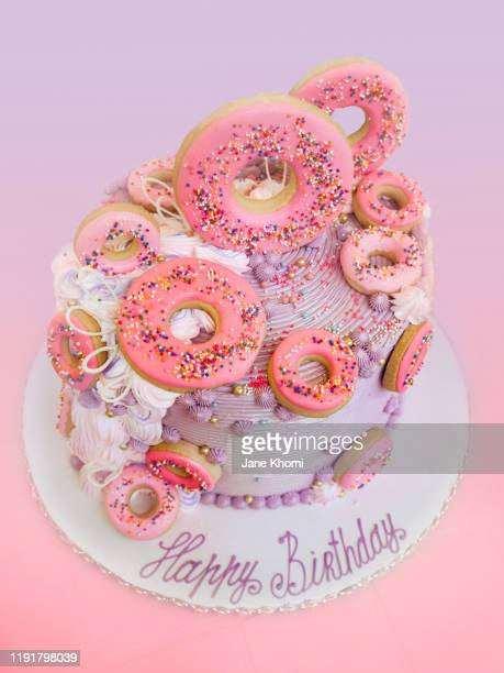 purple and rose birthday cake with donut decoration - icing stock pictures, royalty-free photos & images