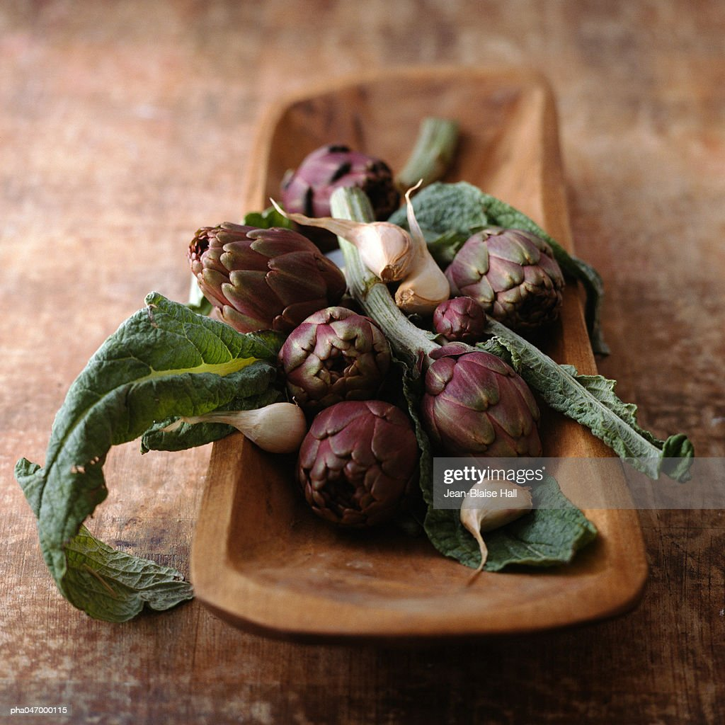 Purple artichokes with leaves and garlic cloves in wooden container, close-up : Stock Photo