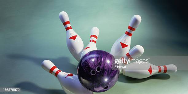 A purple bowling ball knocking over pins