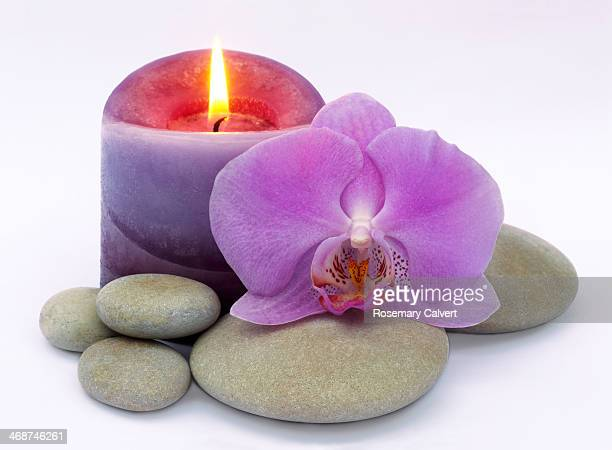 Purple candle burning beside orchid and pebbles