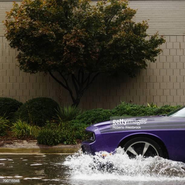Purple car splashing through water in flood