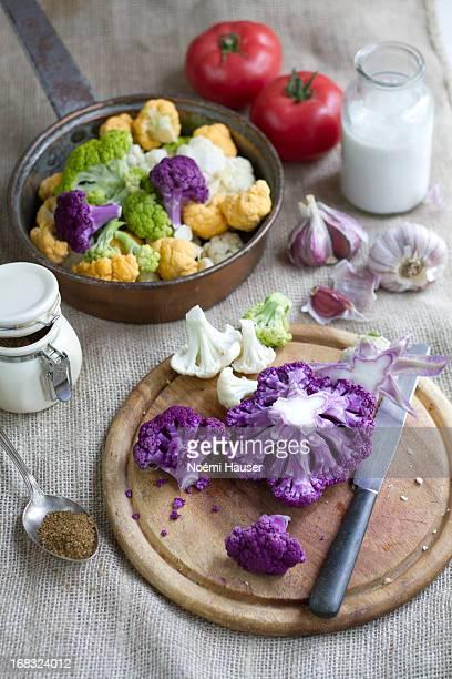 Purple cauliflower florets on wooden board