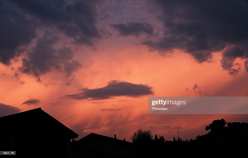 purple clouds gather in a pink sky above dark houses : Stock Photo