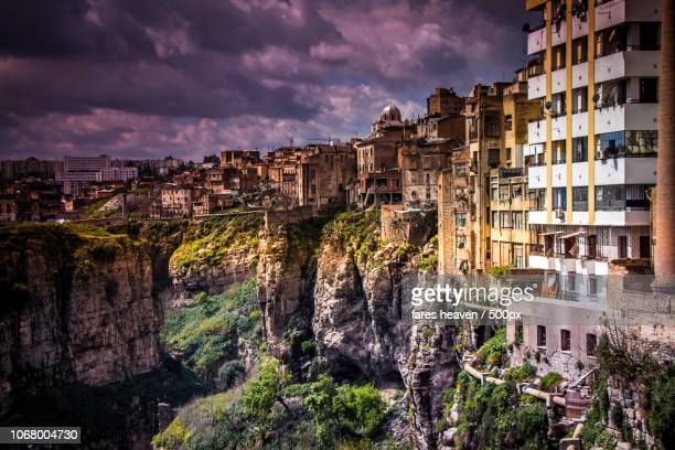 purple clouds over cliffside city buildings - algeria stock pictures, royalty-free photos & images