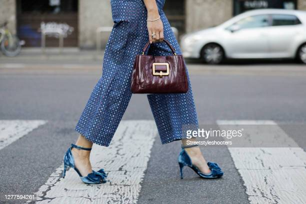 Purple colored bag by Bally and blue heels by Custommade as a detail of influencer Sarah Lou Falk, seen during the Milan Women's Fashion Week on...