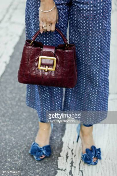 A purple colored bag by Bally and blue heels by Custommade as a detail of influencer Sarah Lou Falk seen during the Milan Women's Fashion Week on...