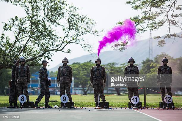 Purple colored smoke is emitted from the top of a dummy target's head at a shooting exercise during an open day at the People's Liberation Army Shek...