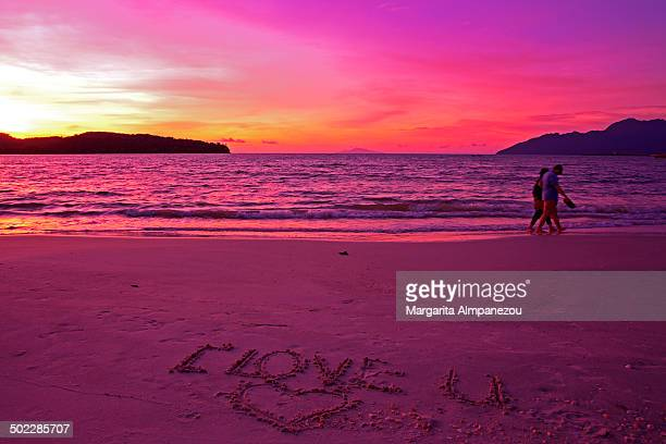 """Purple colors of sunset and """"I LOVE YOU"""" written on the sand from a couple"""