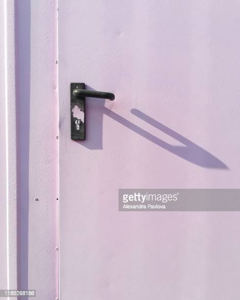 purple door lit by sun forming peculiar doorknob shadow - alexandra pavlova stock pictures, royalty-free photos & images