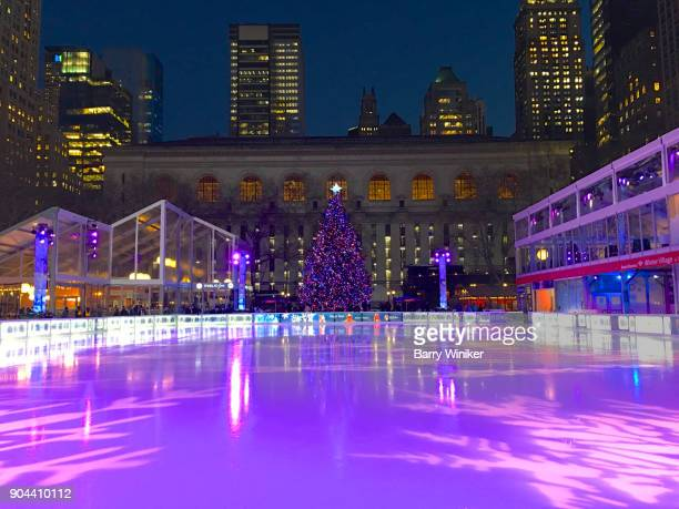 purple glow on ice rink at christmas in bryant park, new york - bryant park stock pictures, royalty-free photos & images