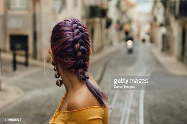 purple haired woman looking at the street of lisbon, portugal - purple hair stock pictures, royalty-free photos & images