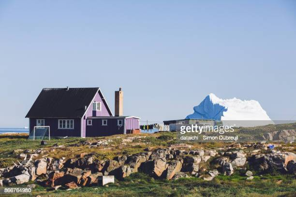 Purple house and iceberg in Qeqertarsuaq on Disko Island
