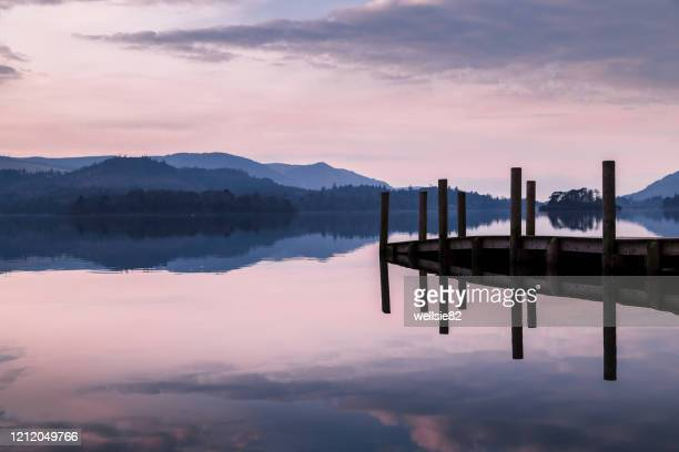 purple hues over derwent water - pier stock pictures, royalty-free photos & images