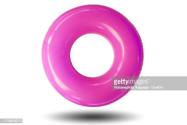 purple inflatable ring against white background - inflatable ring stock pictures, royalty-free photos & images