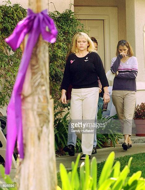 A purple ribbon hangs from a tree as Brenda van Dam mother of missing 7yearold Danielle van Dam walks out of her house along with Diane Halfman to a...