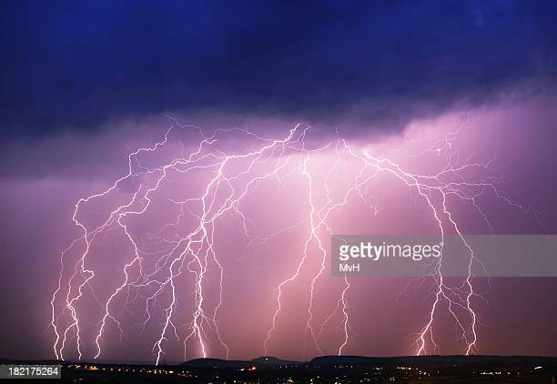 A purple sky with dark clouds and lightning hitting a town