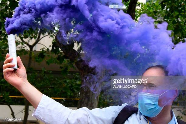 Purple smoke billows from a canister brandished by a health worker during a demonstration, as part of a nationwide day of protests to demand better...