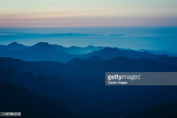 purple sunset colors and layers of central cascades at mount rainier - cascade range stock pictures, royalty-free photos & images