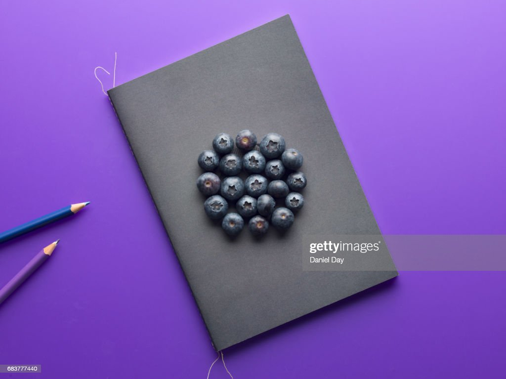 Purple surface shot from above with a notepad and blueberries : Stock Photo