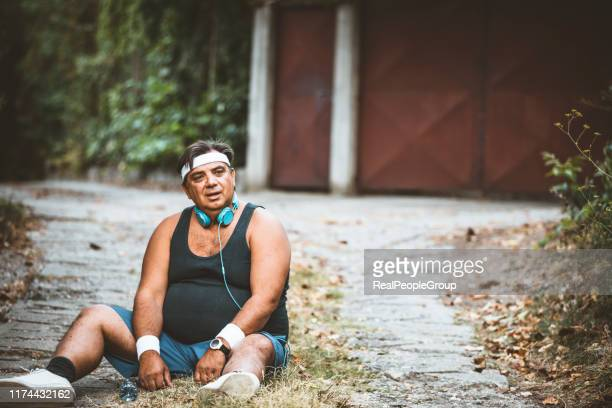 purposeful fat man running in park, out of breath, persistent motivation - headband stock pictures, royalty-free photos & images