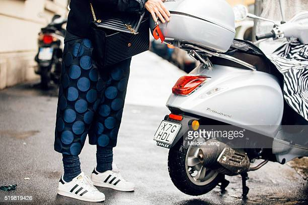 YSL purse blue polkadot pants and Adidas superstar sneakers seen after the Calvin Klein presentation during Milan Fashion Week Fall/Winter 2016/17 on...