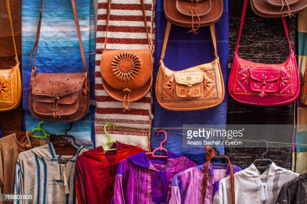 purses hanging in store for sale at market - multi coloured purse stock photos and pictures