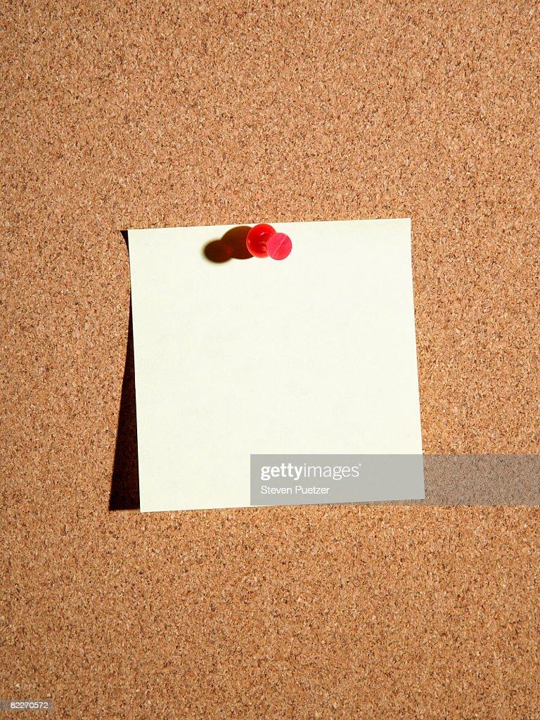 Push pin attaching adhesive note to cork board : Stock Photo