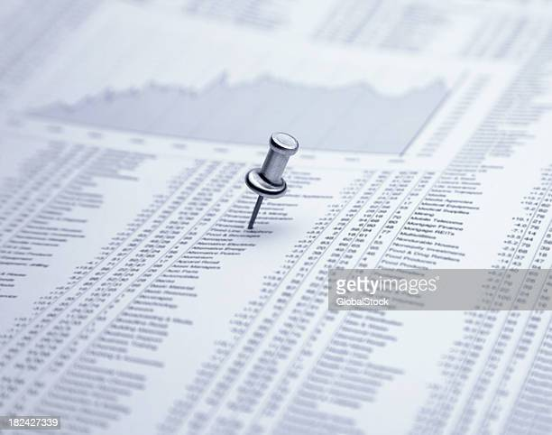 Push pin on financial newspaper