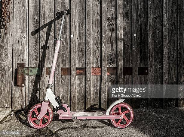 Push Scooter Against Wooden Fence