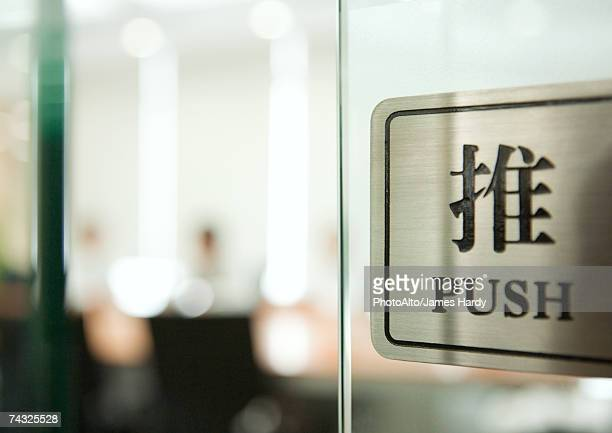Push sign on door in English and Chinese