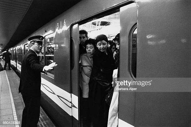 Pushers ensure all passengers are safely onboard a train in Tokyo Japan March 1988