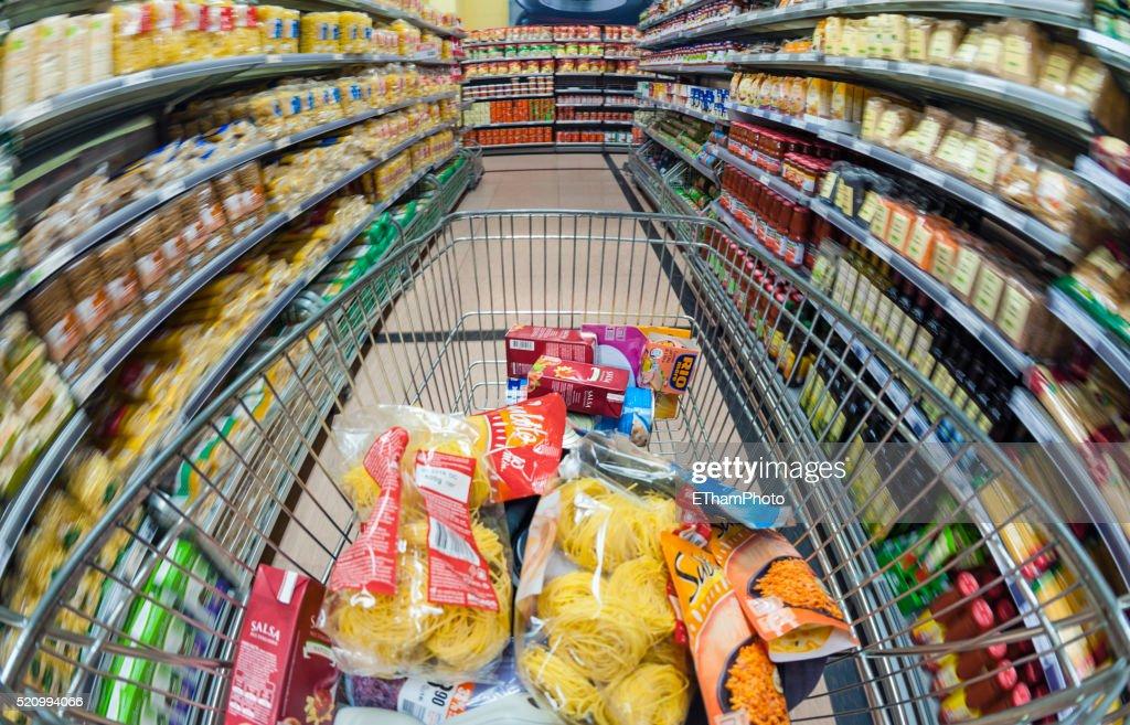 Pushing a shopping cart through the supermarket : Stock Photo