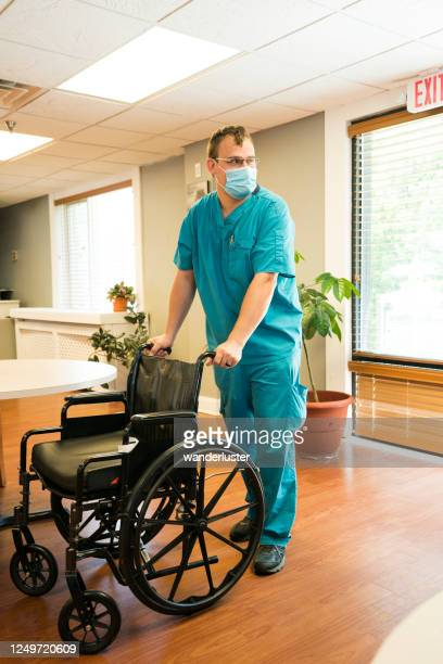 pushing an empty wheelchair - infectious disease stock pictures, royalty-free photos & images