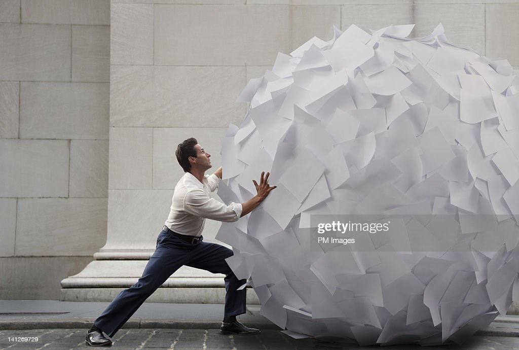 Pushing big ball of paper : Stock Photo