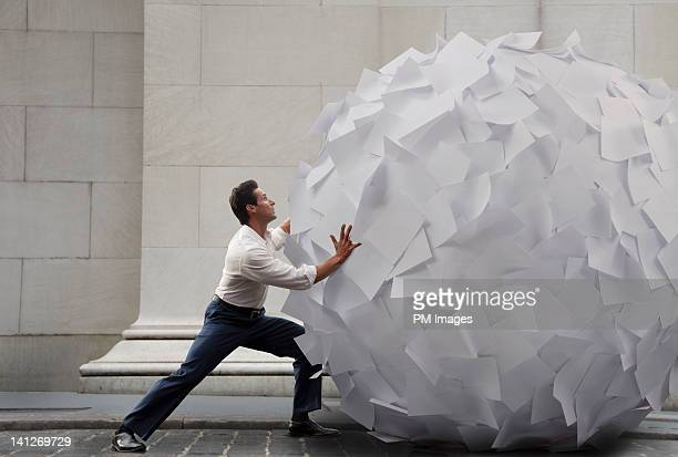 pushing big ball of paper - man with big balls stock photos and pictures