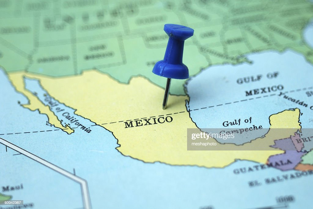 a pushpin marking mexico as a travel destination on a map stock photo