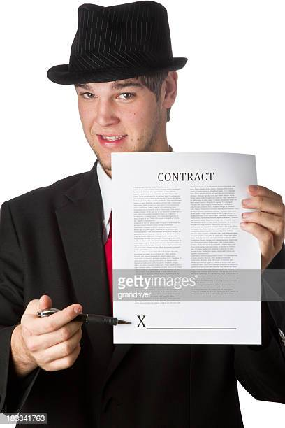 pushy salesman with fedoranwith contract isolated on white - con man stock photos and pictures