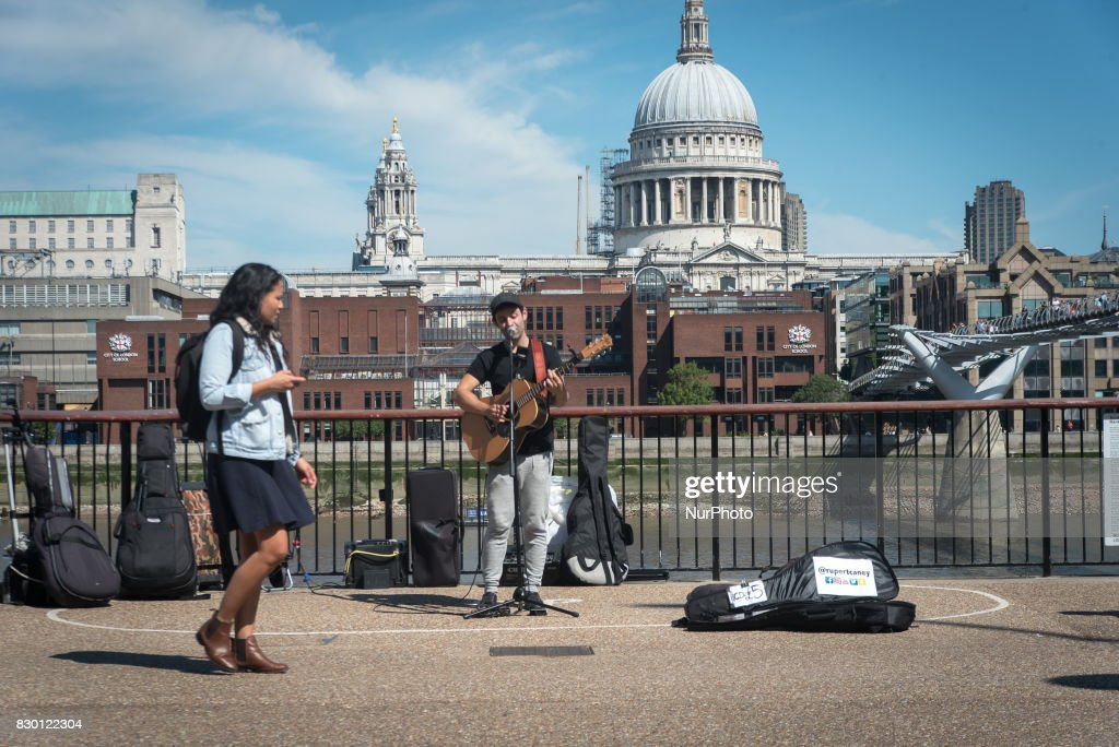A pusker is pictured while he performs, against the backdrop of St. Paul's Cathedral, in a sunny morning in the Southbank of London, on August 11, 2017. The South Bank is an entertainment and commercial district of central London, next to the River Thames opposite the City of Westminster. It forms a narrow, unequal strip of riverside land within the London Borough of Lambeth and the London Borough of Southwark where it joins Bankside. As with most central London districts its edges evolve and are informally defined however its central area is bounded by Westminster Bridge and Blackfriars Bridge. It includes points of interest such as the iconic London Eye, Southbank Centre, National Theatre and Tate Modern.