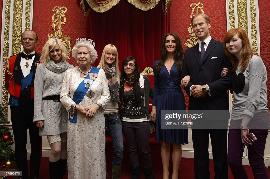 Pussycat Doll Kimberly Wyatt poses with fans next to wax figures of the Royal family including Prince Philip, Duke of Edinburgh, Queen Elizabeth II, Catherine, Duchess of Cambridge and Prince William, Duke of Cambridge at Madame Tussauds on December 7, 2012 in London, England.