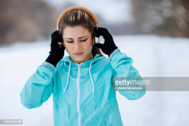 girl snow putting headphones before running