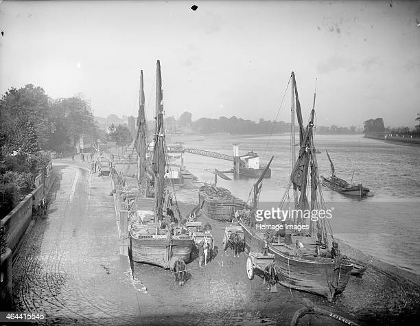 Putney Wharf, Putney, Greater London, 1895. Looking from Putney Bridge along the wharf with a number of boats loading and unloading goods onto carts.