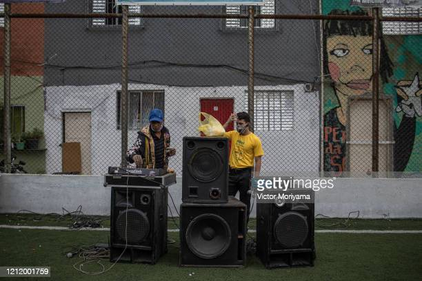 DJ puts music as residents of the Paraisópolis slum provide first aid training on May 6 2020 in Sao Paulo Brazil The local community organizes itself...