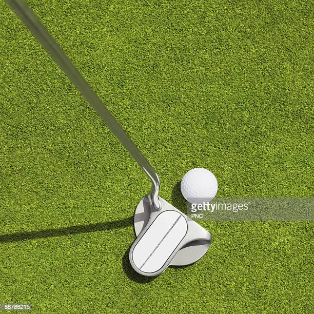 Putter and ball on green