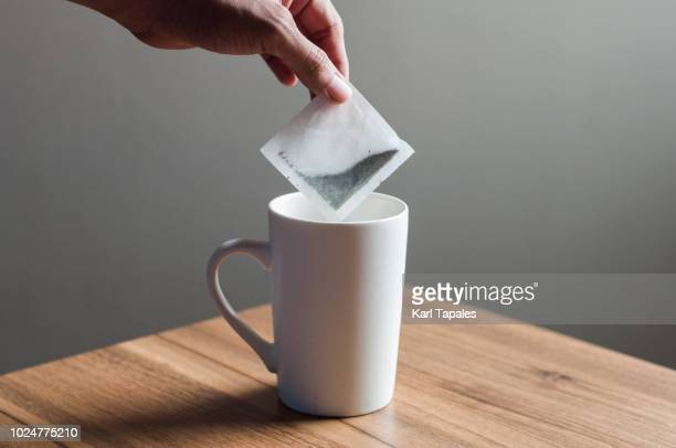 Putting a tea bag into a white mug