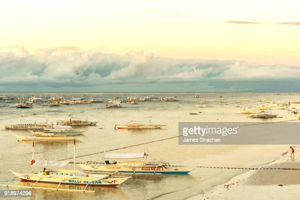 Putting a toe in the water at dawn by all the bangkas (outrigger canoes) berthed by Panglao Beach, Bohol Island, Philippines