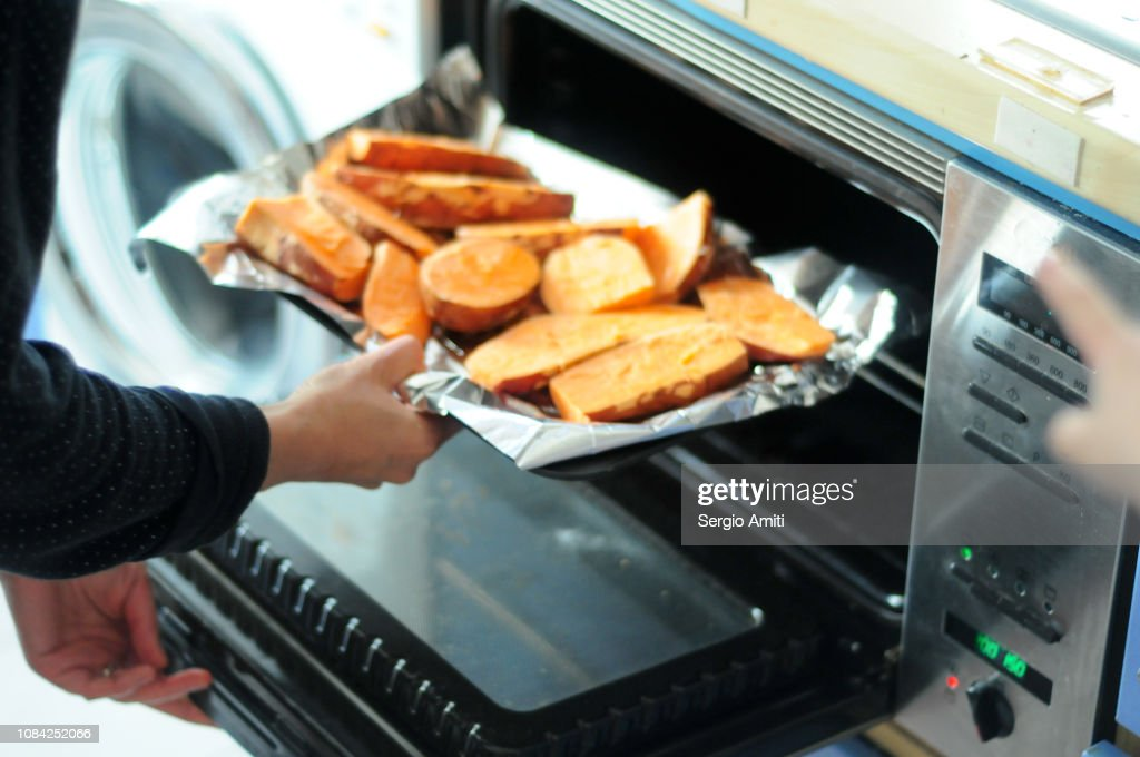 Putting a tray of sweet potatoes in the oven : Stock Photo