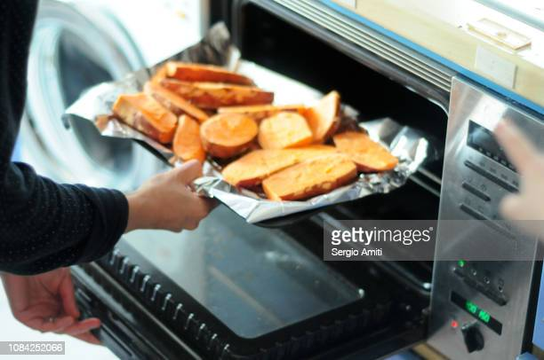 Putting a tray of sweet potatoes in the oven