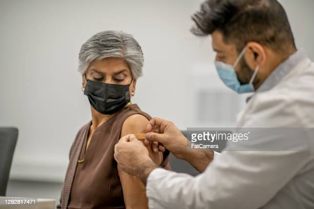 putting band aid on after vaccination - fatcamera stock pictures, royalty-free photos & images